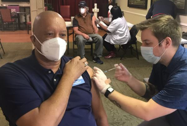 A man in a mask receives a vaccination from a health care worker in a mask